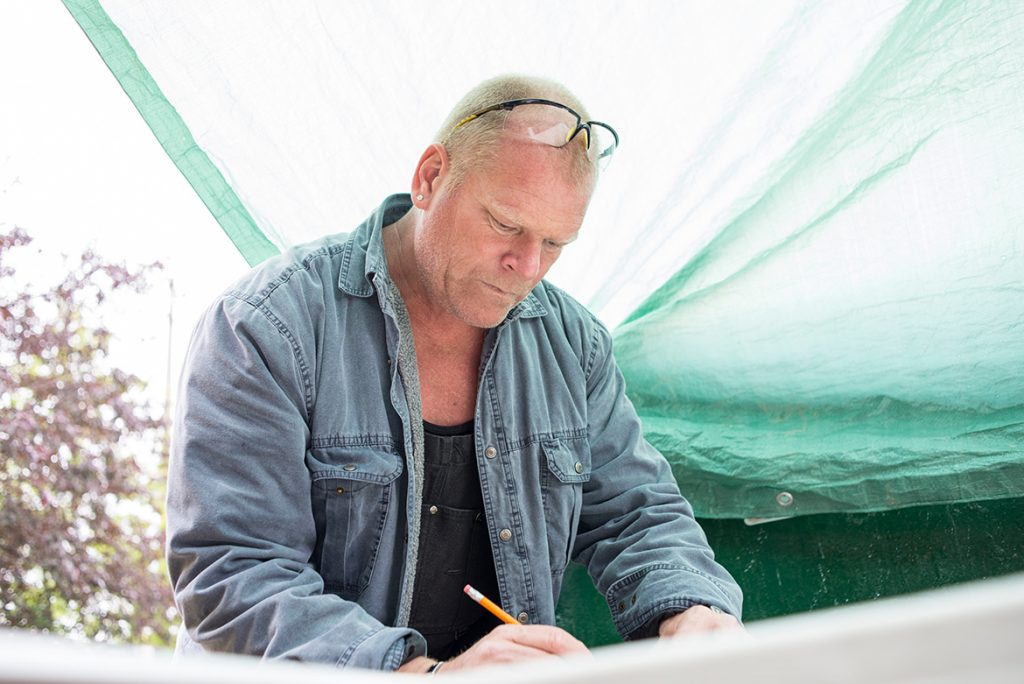 Mike Holmes looking at papers how to hire a contractor